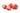 Drei ganze und eine aufgeschnittene Erdbeere mit gruenen Blaettern auf weißem Hintergrund