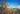 Naturaufnahme voller Sanddornzweig mit orange farbenen Beeren und dunkelgruenen Blaettern mit blauem Himmel und Leuchtturm im Hintergrund