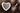 Weiße Porzellanschale in Herzform gefuellt mit dunklen Chiasamen und kleiner silberfarbener Löffel mit Chiasamen auf dunklem Holztisch