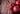 Zwei ganze Granatäpfel und eine geöffneter Granatapfel mit einzelnen Kernen auf dunklem Holztisch