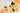 Geschnittene Orangenscheiben mit dunkelgruenen Blaettern und kleiner Oelflasche auf weißem Holztisch