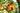 Weißer porzellanteller mit frischem blattsalat mit wildblumen auf dunklem holztisch in nahaufnahme