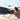 dunkelhaarige frau im sommerkleid kniet am strand und malt mit stock fragezeichen in den sand