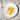 Weißer Porzellanteller mit einer Honigwabe und einem Honigloeffel auf Holztisch