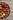 Schale mit braunen und gruenen Jojobafruechten auf Holztisch